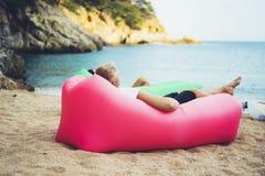 年轻行家放松在可膨胀的懒惰空气蒲团沙发的海岸线海滩的,人游人享受在背景海岸的晴天 免版税库存图片