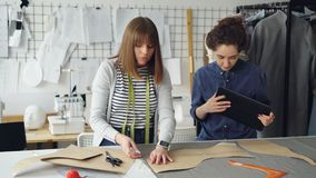 年轻裁缝与片剂一起使用,传达并且概述在纺织品的衣物样式在演播室书桌上 光 股票视频