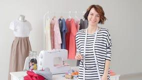 小企业和爱好概念 年轻裁缝微笑着以他们的产品为背景在他的演播室 股票视频