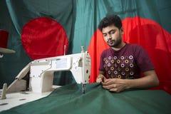 年轻裁缝Md Rashed Alam,在达卡,孟加拉国变老28面制造的孟加拉国的国旗 图库摄影