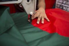 年轻裁缝Md Rashed Alam,在达卡,孟加拉国变老28面制造的孟加拉国的国旗 免版税库存照片