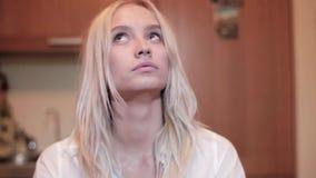 年轻褐色有好奇面孔的被注视的相当白肤金发的女孩凝视天花板 股票录像