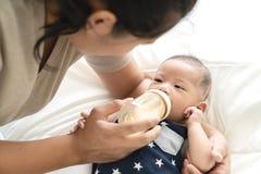 年轻西班牙从人工喂养从年轻父母母亲或保姆的塑料的婴孩或亚裔婴儿男孩饮用奶 免版税库存图片
