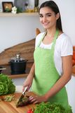 年轻西班牙妇女在厨房里烹调 主妇切菜和青菜新鲜的沙拉的 库存照片
