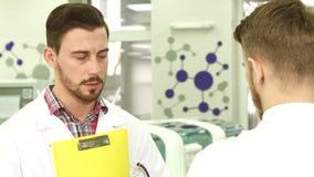 年轻试验室工怍人员进行关于工作的严肃的交涉 图库摄影