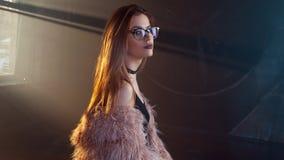 年轻诱人的妇女,画象在黑暗中 时髦的桃红色皮大衣和玻璃的女孩 免版税库存照片