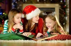 年轻读书的母亲和她的小女儿由一棵圣诞树在舒适客厅在冬天 免版税库存图片