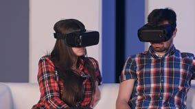年轻调整虚拟现实玻璃的人和妇女对手表电影 免版税库存照片