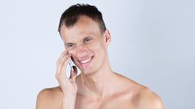 年轻赤裸上身的人谈话在他的手机 免版税库存照片