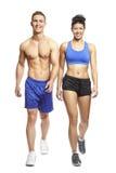年轻走在体育运动成套装备的人和妇女 免版税图库摄影