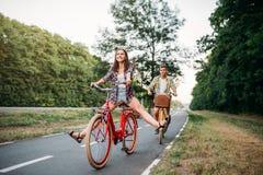 年轻走在减速火箭的自行车的人和妇女 库存图片