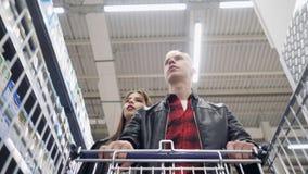 年轻走在超级市场和chooce产品的夫妇人和女孩 股票录像