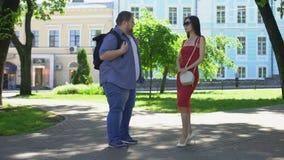 年轻超重人谈话与亭亭玉立的夫人在公园,忽略肥胖人的俏丽的女孩 股票录像