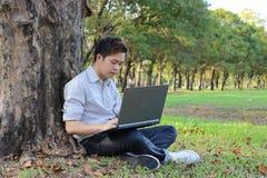 年轻轻松的人在室外公园使用一台膝上型计算机 放松和技术概念 库存照片