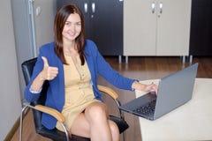 年轻辅助工作在膝上型计算机的办公室 库存图片