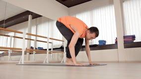 年轻运动人在瑜伽姿势坐在健身房的蓝色席子与镜子 瑜伽,体育,放松,灵活 股票录像
