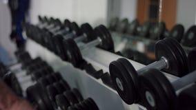 年轻运动员采取哑铃并且在镜子前面安置它在健身房 股票录像