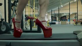 年轻运动女孩,运动,执行在踏车的一锻炼 在她的脚她穿了在一个高平台的鞋子 股票视频