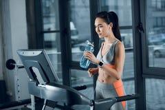 年轻运动女运动员饮用水,当跑步在踏车时 库存照片