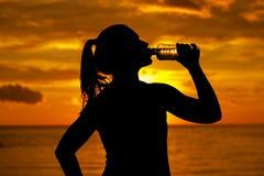 年轻运动妇女饮用水剪影  库存图片