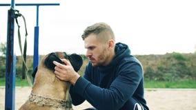 年轻运动的人拥抱和演奏他的bullmastiff狗室外在自然 库存图片