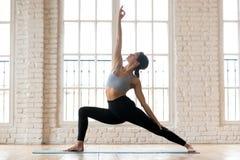 年轻运动的可爱的女子实践的瑜伽,做反向战争 免版税库存图片