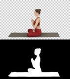 年轻运动的可爱的女子实践的瑜伽,做莲花姿势,阿尔法通道 库存图片