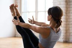 年轻运动的可爱的女子实践的瑜伽,Paripurna Navasan 免版税库存照片