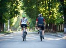 年轻运动的夫妇骑马自行车在公园 免版税图库摄影