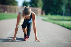 年轻运动的妇女画象一件蓝色衬衣的和绑腿是在开始的准备好和立场在体育场轨道 免版税库存照片
