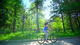 年轻运动的愉快的妇女通过夏天公园骑自行车 外面自行车的女孩 新的成人 晴朗的日 太阳强光 影视素材