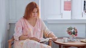 年轻迷人的妇女在家坐椅子和阅读书在窗口旁边 免版税库存图片