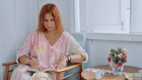 年轻迷人的妇女在家坐椅子和阅读书在窗口旁边 图库摄影