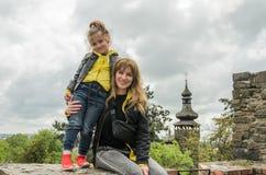 年轻迷人的母亲和女儿一个老堡垒的废墟的以教会圆顶为背景 免版税库存图片