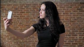 年轻迷人的深色的女孩在她的智能手机做selfie,摆在,通信构想,砖背景 影视素材