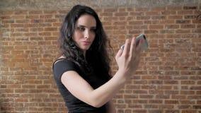 年轻迷人的深色的女孩在她的智能手机做selfie,通信构想,砖背景 股票录像