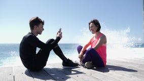 年轻适合的人坐拍他的有电话的女朋友的照片海滩 飞溅反对岩石的强的波浪 影视素材