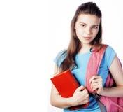 年轻逗人喜爱十几岁的女孩摆在快乐反对与被隔绝的书和背包,生活方式人的白色背景 库存照片