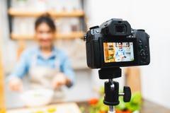 年轻逗人喜爱的亚裔在家烹调教训厨房的沙拉博客作者女孩记录的录影讲解会议 食物博克的概念 免版税库存照片