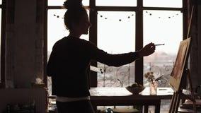 年轻逗人喜爱的卷曲女性艺术家跳舞在艺术演播室然后结束在她的绘画的线,有背景 股票视频