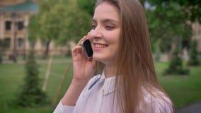 年轻逗人喜爱的女孩在电话谈话在公园在夏天,情感概念,通信概念 股票视频