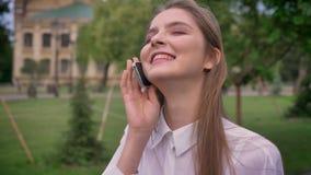 年轻逗人喜爱的女孩在电话谈话在公园在夏天,笑,通信概念 股票视频