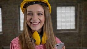 年轻逗人喜爱的女孩建造者在她的smarphone,笑,通信构想观看 股票录像