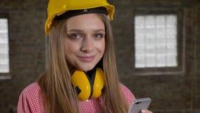 年轻逗人喜爱的女孩建造者观看她的智能手机,在照相机的watchig,微笑,通信概念 股票录像