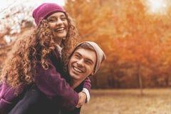 年轻逗人喜爱的女性拥抱男朋友 免版税库存照片
