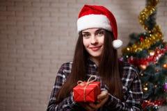 年轻逗人喜爱的妇女画象圣诞老人盖帽的有在chri的一个礼物的 免版税图库摄影