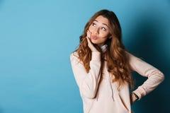 年轻逗人喜爱的妇女身分被隔绝在蓝色墙壁 免版税库存照片