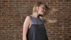年轻逗人喜爱的白肤金发的女孩使用与头发,调情的人概念,砖背景 股票视频