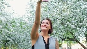 年轻逗人喜爱的被刺字的妇女在开花的苹果树采取在手机的selfie 影视素材