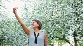 年轻逗人喜爱的被刺字的妇女在开花的苹果树采取在手机的selfie 股票视频
